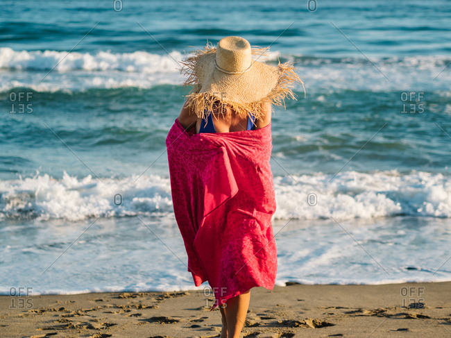 Joyful unrecognizable woman in hat and dark blue swimsuit wrapped in pink scarf and walking along seaside in sunny bright day