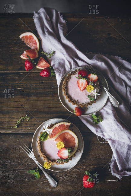From above portions of delicious strawberry and citrus cakes served on decorated wooden table