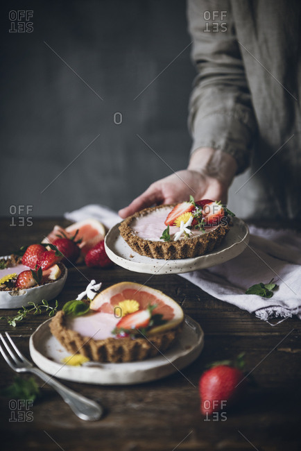 Crop person carefully serving plate of garnished citrus cake with strawberry on wooden table