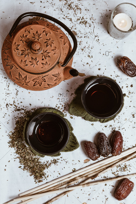 From above fragrant tasty tea in cup clay teapot and sweet dates on white tray decorated with tea leaves on wooden background