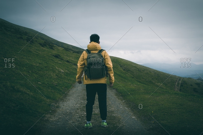 Back view of unrecognizable male with backpack standing on rough path on grassy hill slope against gray overcast sky in nature