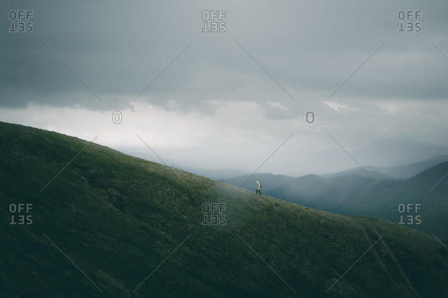 Back view of unrecognizable male with backpack walking on rough path on grassy hill slope against gray overcast sky in nature