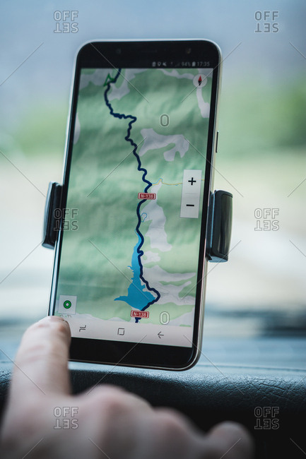 Closeup hand of anonymous tourist using gps navigator on modern smartphone in car during road trip