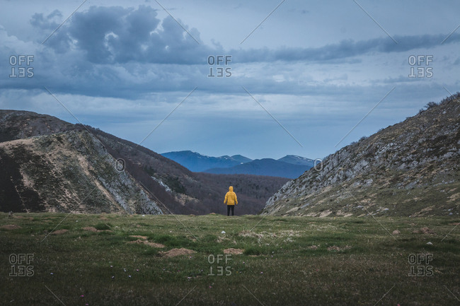 Back view of tourist in yellow coat looking at rough hills and overcast sky during trip in countryside