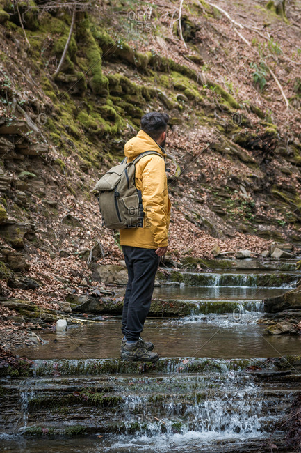 Side view of anonymous man with backpack standing on natural steps with flowing water and in mountainous terrain
