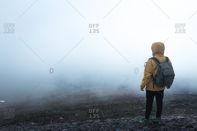 Back view of guy with backpack standing on hillside against thick fog during trip in nature