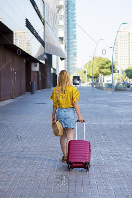 Back view of young beautiful female tourist going on adventure with suitcase on the street
