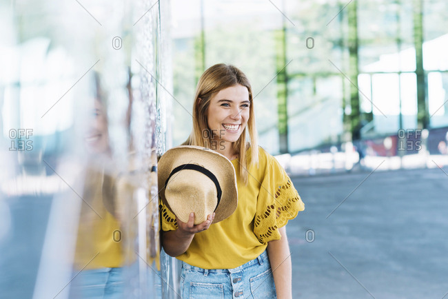 Young blonde woman with beautiful blue eyes leaning in a wall holding a straw hat