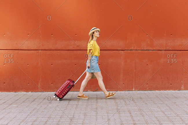 Side view of young beautiful female tourist going on adventure with suitcase