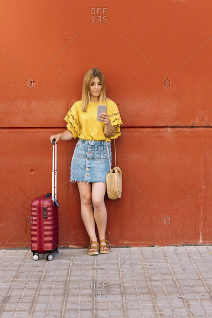 Young woman tourist talking on mobile phone leaning on red wall