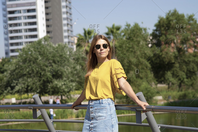 Young stylish beautiful female model wearing sunglasses leaning on handrail in park