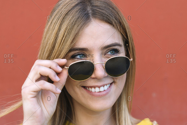 Beautiful young woman with blue eyes taking off sunglasses and smiling away
