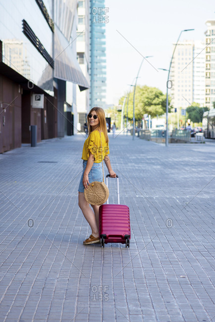 Side view of young beautiful female tourist going on adventure with suitcase on the street
