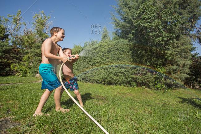 Little children in swimwear splashing water holding garden hose together