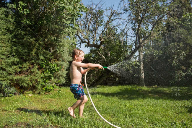 Little laughing kid in shorts and with bare feet splashing water from garden hose