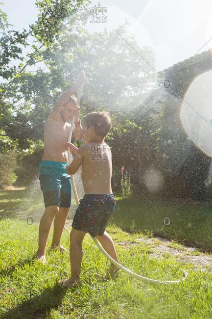 Little children in swimwear running around and splashing water from garden hose at each other