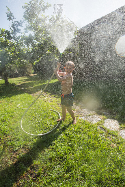 Little laughing kid in shorts and with bare feet splashing water towards camera from garden hose