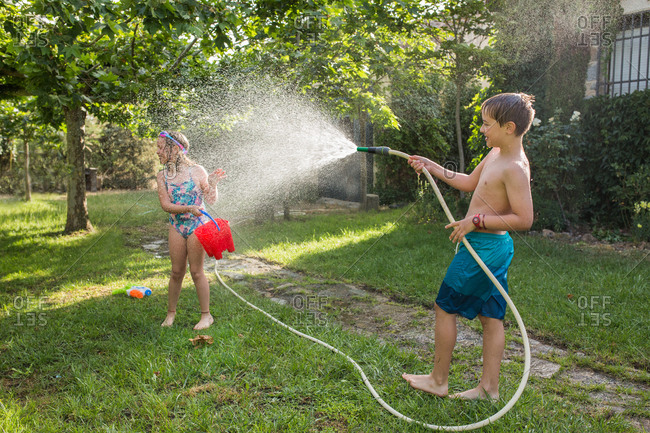 Boy in swimwear splashing water from garden hose at a girl on a sunny day