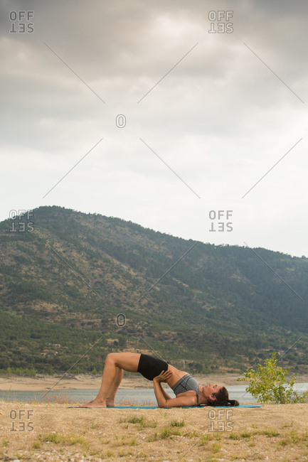 Young woman doing yoga poses outdoors on a cloudy day next to a dam beach