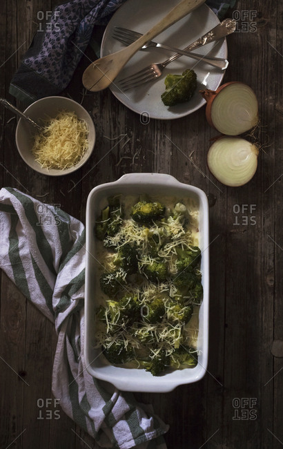 From above ceramic baking pan of tasty roasted broccoli with shredded cheese and onion placed near napkin and dishware on timber tabletop