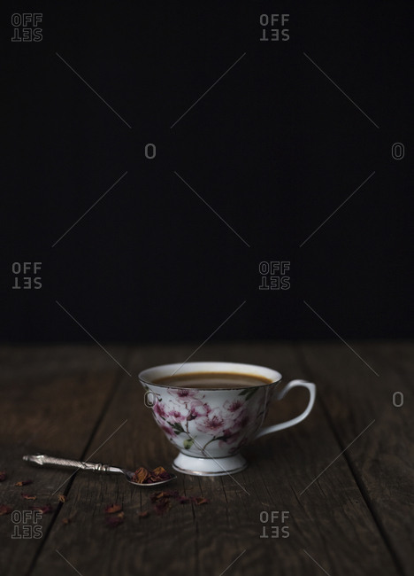 Small spoon with shredded chocolate placed near cup of fresh hot coffee on wooden tabletop against black background