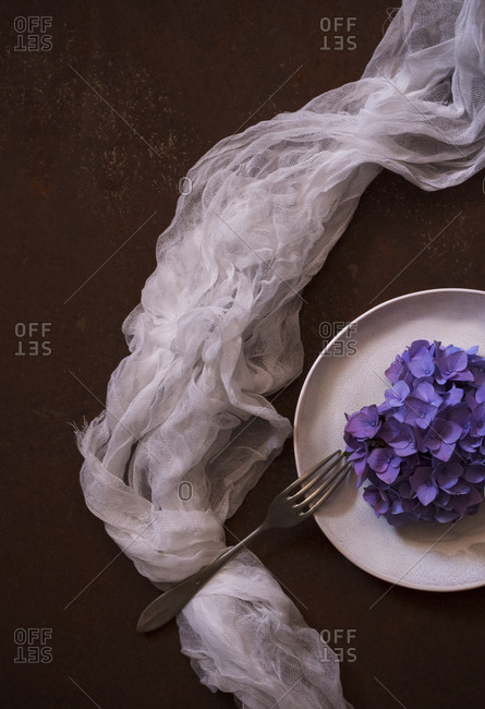 From above thin translucent fabric placed near plate with heap of violet flowers on brown surface