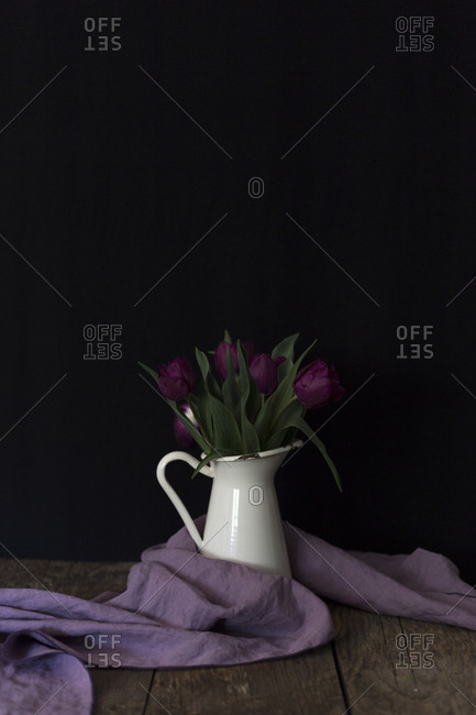 Tiny metal bucket with bright purple flowers placed on lumber tabletop