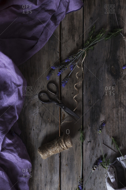 From above linen rope and vintage scissors placed on timber tabletop near violet fabric and fresh lavender