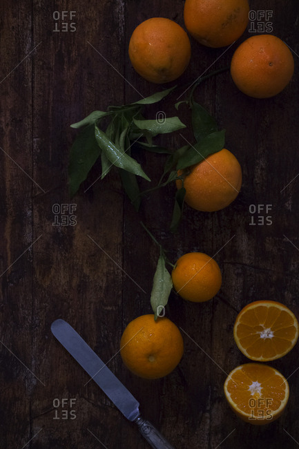From above metal knife placed on dark wooden tabletop near cut and whole fresh juicy oranges