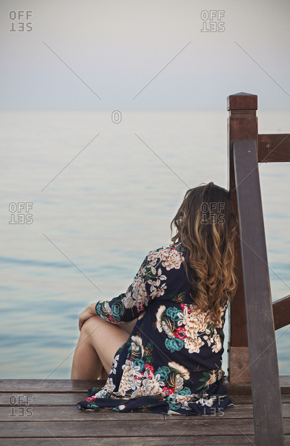 Young brunette woman resting on dock near water surface and looking at coastline