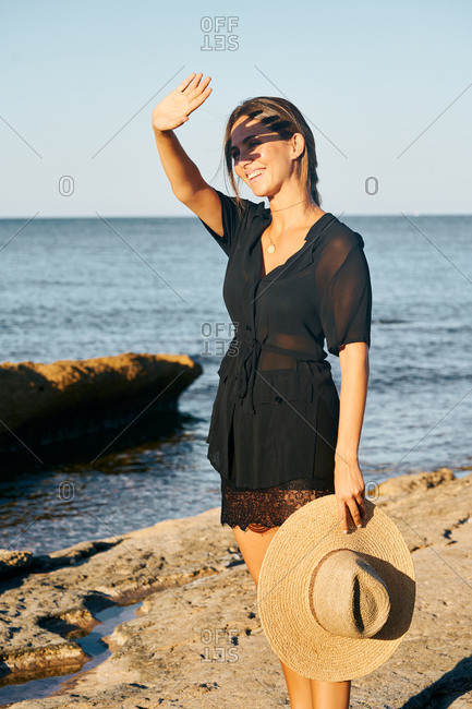 Young beautiful female model enjoying sun covering face from sun on beach holding hat