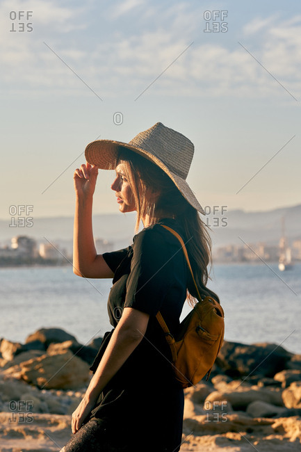 Side view of female tourist wearing a straw hat and backpack standing near beach