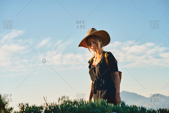 Side view of female tourist wearing a straw hat and backpack walking
