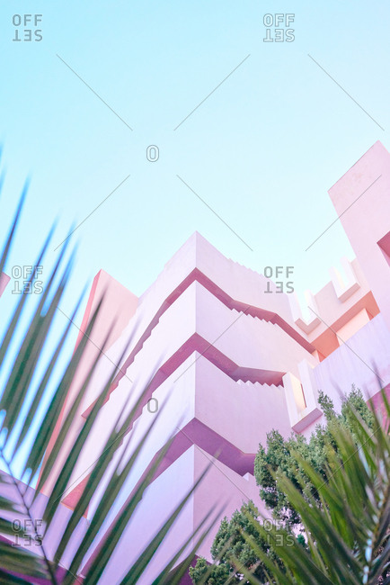 From below end of pink building of complex geometric shape