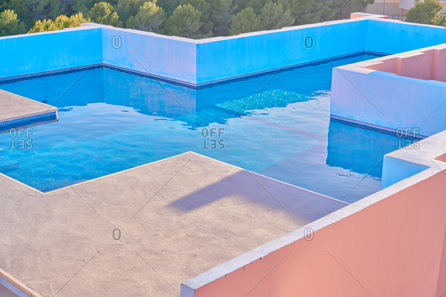 From above luxurious pool with fresh cool water on roof of interesting shaped building in bright sunny day