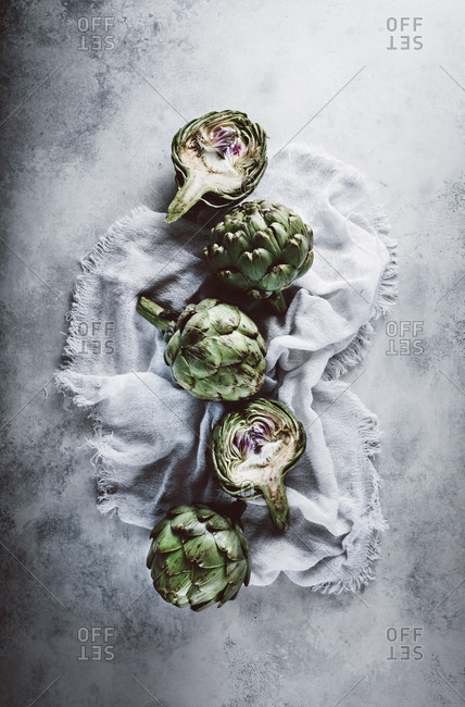 Artichokes on linen cloth on gray background