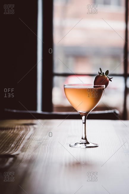 Cocktail garnished with a strawberry on a bar