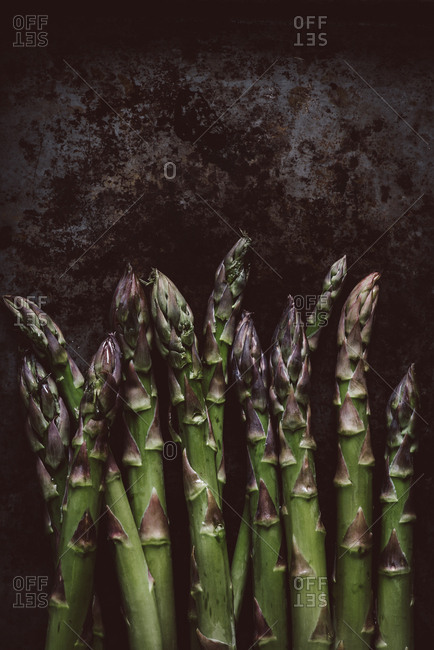Close up of green asparagus on dark rustic background