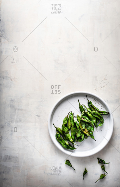 Shishito peppers on plate on white background