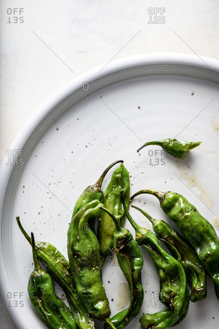 Close up of shishito peppers on plate on white background