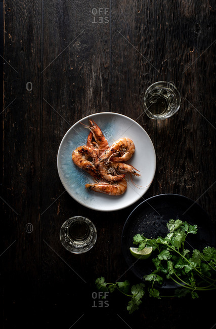 Overhead view of shrimp and cilantro on dark wooden background