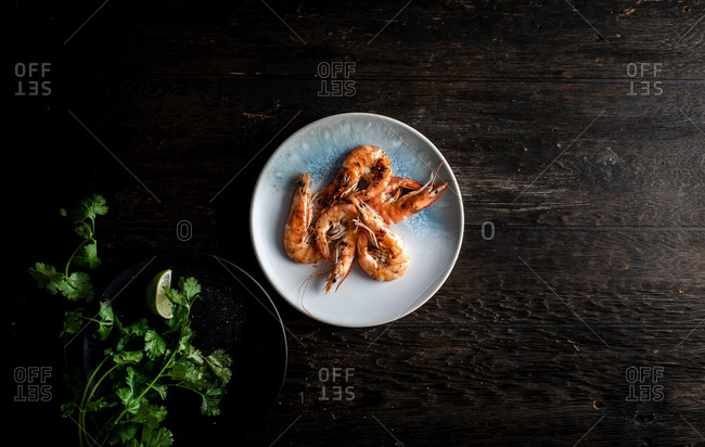 Shrimp and cilantro on plates on dark wooden background