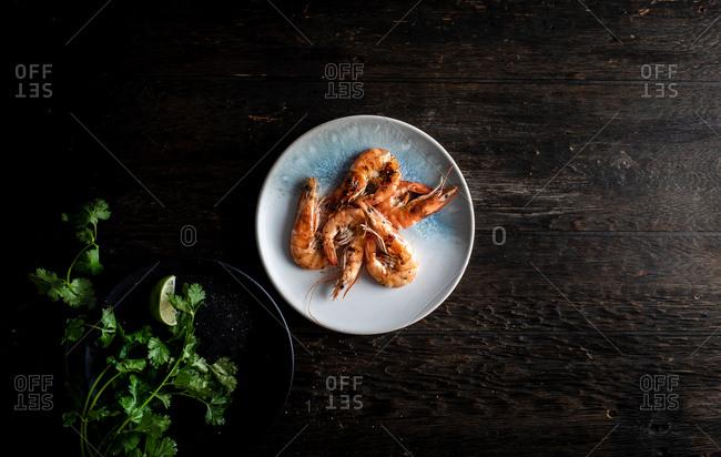 Shrimp and cilantro on plates on dark wooden background