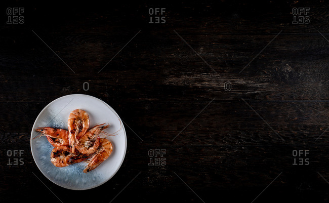 Plate of shrimp on dark wooden background