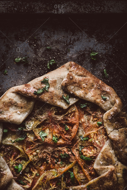 A fresh baked tomato galette on rustic background