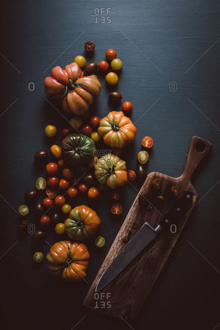 Variety of heirloom tomatoes on dark background with cutting board and knife
