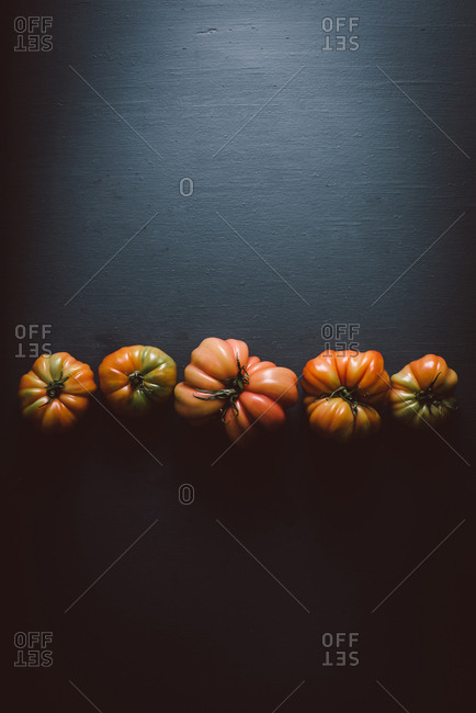 Heirloom tomatoes in a row on dark background