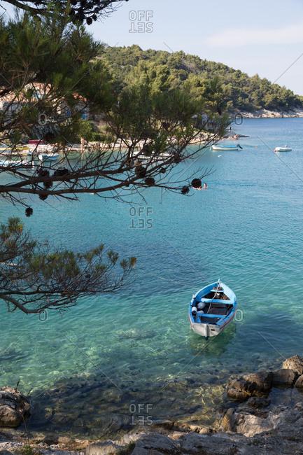 Croatia - August 8, 2019: People swimming near boats moored in the Adriatic Sea on the Croatian coast