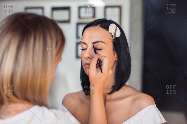 Makeup artist applying model's eyebrow makeup before photo shoot