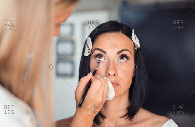 Cosmetologist applying model's eye makeup before photo shoot